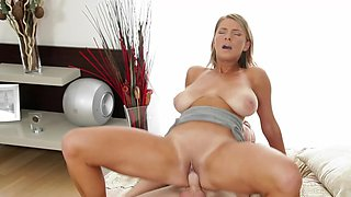 A blonde with saggy tits and tan lines is penetrated on the bed deeply