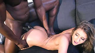 A white woman is getting fucked by a black dude on the sofa
