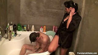 Palatable brunette in gown provides her boyfriend with a handjob in the shower
