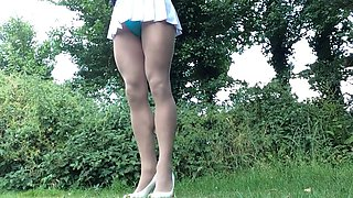 Crossdresser removing skirt to swimsuit outdoors.